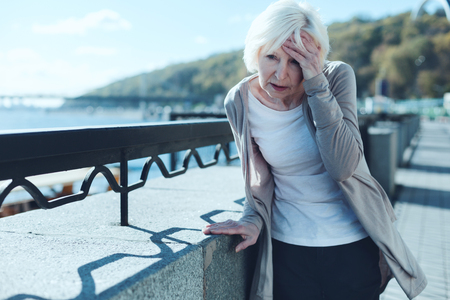 Need to take my pills. Exhausted older lady leaning on a barrier and touching her forehead while suffering from a terrible headache outdoors. Stok Fotoğraf
