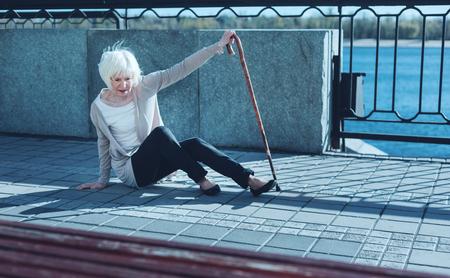Lo que acaba de suceder. Perpleja anciana apoyada en un bastón mientras trata de comprender lo que sucedió y ponerse de pie después del vértigo. Foto de archivo