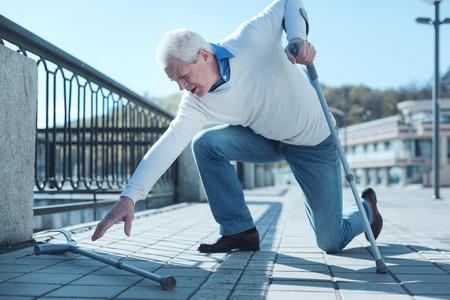 Debería tener más cuidado. Hombre jubilado cansado apoyado en una muleta mientras intenta levantar otra después de caer al suelo durante una caminata diaria.