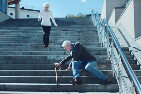 I am running honey. Loving wife coming down the steps in a rush after seeing her husband falling unexpectedly and cannot move. Banco de Imagens - 97936097