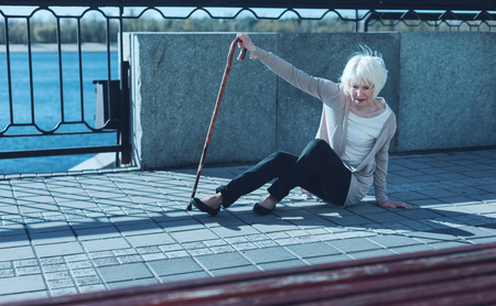 Oh no. Frightened retired woman leaning on a walking cane while trying to stand up after falling to the ground. Stock Photo