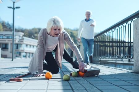 Geht es dir gut Selektiver Fokus auf einer erschrockenen älteren Dame, die auf ihrem Knie steht und versucht, ihre Lebensmittel abzuholen, nachdem sie heruntergefallen sind, während ihr besorgter Ehemann zu ihr in den Hintergrund läuft.