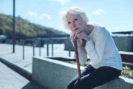 私が若い頃。歩く遊歩道の上に手とあごを置いて外に座り、過去を思い出しながら空席を見つめるペンシブな年配の女性。 写真素材 - 97936103