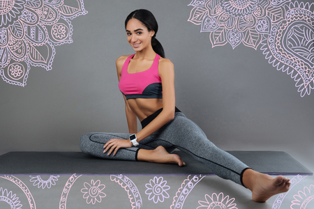 Healthy lifestyle. Beautiful young slim girl keeping fit and looking glad while sitting on a convenient yoga mat and doing exercises