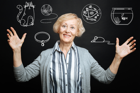 Pets lover. Cheerful kind senior lady smiling and putting her hands up while being alone and thinking about her cute adorable pets