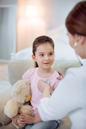 Childs needs. Appealing beautiful girl posing on blurred background and embracing plush bear while female doctor using stethoscope
