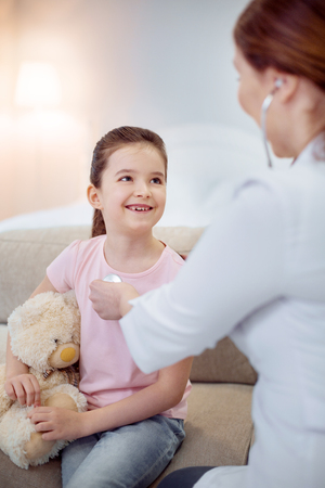 Unusual illness. Glad cheerful girl laughing and touching plush bear while female doctor using stethoscope Stock Photo