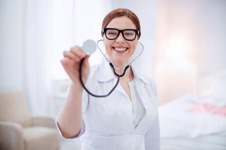 Doctors tool. Appealing skillful experienced female doctor staying on blurred background while grinning and rising stethoscope Stock Photo