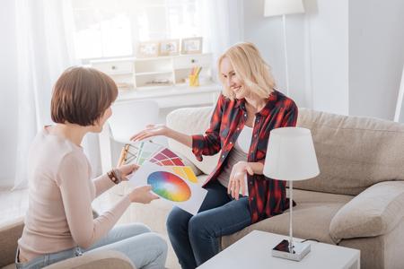 Nuevas tendencias. Felices mujeres positivas positivas sentadas una frente a la otra y discutiendo una paleta de colores mientras eligen un nuevo diseño Foto de archivo