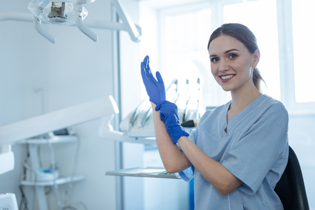Ready to work. Beautiful young female dentist putting on rubber gloves and smiling at the camera while getting ready for the treatment