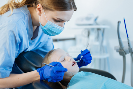 Nice service. Cute petite girl lying in a dentist chair with her eyes closed and having her teeth examined by a caring female dentist using a mouth mirror and a dental probe Archivio Fotografico