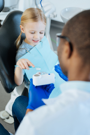 Lovely little girl using a toothbrush and practicing correct teeth brushing while being guided by her male dentist