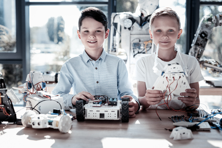 Innovative generation. Waist up shot of smart kids looking into the camera with cheerful smiles on their faces while posing with their self automated robots in hands.