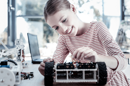 This one is even better than my previous. Smart young lady sitting at a table and enjoying the process of creation while working on her new robotic machine. Stock Photo