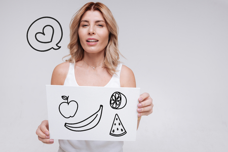 Fresh fruit. Cheerful young woman leading a healthy lifestyle and feeling glad while thinking of buying delicious fresh fruit