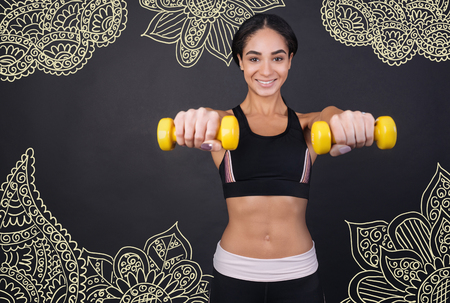 Strong woman. Positive young smiling sportswoman feeling happy while being in her favorite gym and training with little yellow hand weights