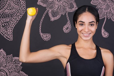 Showing muscles. Cheerful young smiling sportswoman looking strong while holding a little yellow hand weight and bending her arm Banco de Imagens