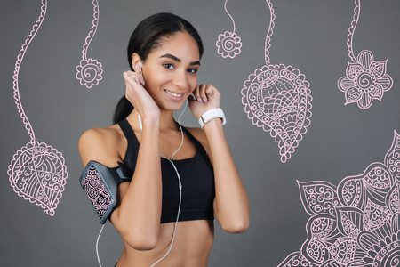Favorite songs. Pretty young emotional sportswoman feeling good and smiling while standing in sporty clothes and listening to music in her convenient little earphones Banco de Imagens