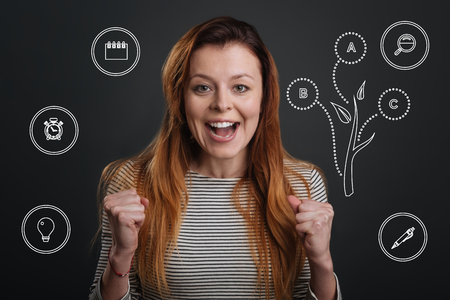 Enthusiasm. Cheerful experienced enthusiastic employee feeling happy and looking ready for a new working day while standing in her office and smiling