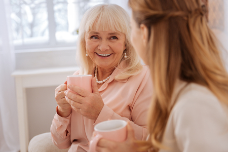 Wonderful mood. Happy delighted aged woman smiling and looking at her daughter while having tea with her