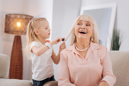 Future hair stylist. Positive cute blonde girl smiling and brushing her grandmothers hair while wanting to be a hair stylist