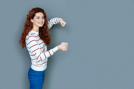 Delicious drink. Happy positive red haired woman smiling and looking at you while preparing tea for herself