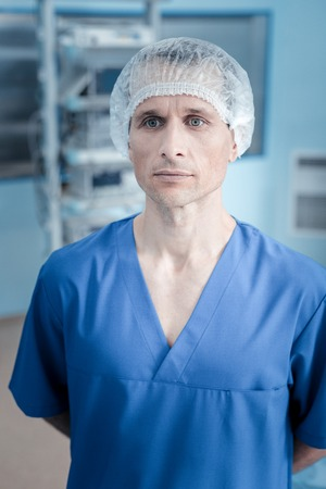 Smart nice handsome surgeon standing in the operation room and wearing medical uniform while being ready to work Stock Photo