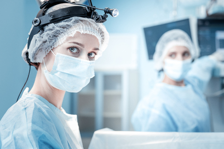 Portrait of a nice smart female surgeon wearing scrubs and looking at you while being in the operation theater