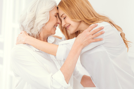 Tender senior mother and her mature daughter smiling and keeping their eyes closed while hugging and expressing their love to each other.