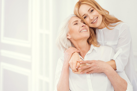 Sweet moment of expressing love between retired mother and her loving daughter wearing matching attire at home. Stock Photo