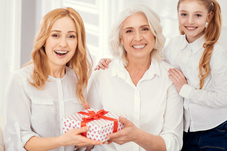 Amazed lady receiving an unexpected gift box from her loving mother and daughter while all three sitting on a sofa and looking into the camera.