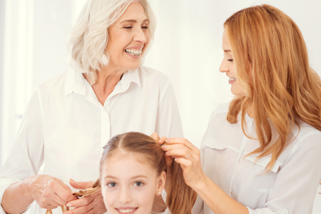 Fun and joyful moment. Selective focus on an excited beautiful elderly lady grinning broadly while talking to her mature daughter and making ponytails for her cheerful granddaughter. Stock Photo
