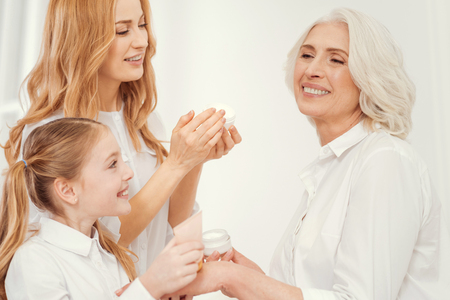Prettier than yesterday. Side view on three generations of women spending free time together and taking care of their skins while applying moisturizing creams of their faces. Stock Photo
