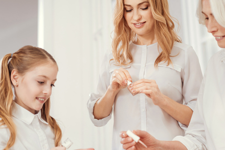Beauties of our family. Selective focus on a beautiful blonde focusing her attention on a bottle of a nude nail polish while doing her manicure in a family circle and having a girly time at home. Stock Photo