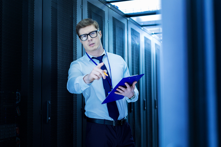 Handsome smart operator holding a folder and pointing with his finger
