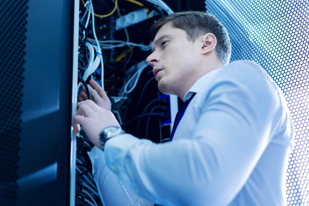 Determine experience man working in a service cabinet and repairing wires Stock Photo