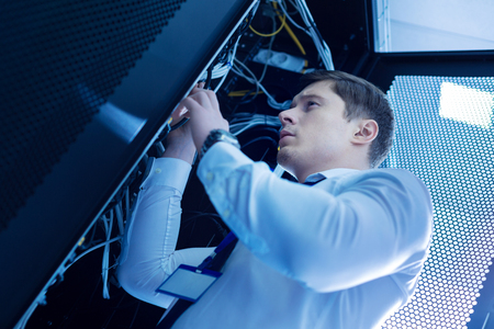 Professional experienced man working in a service cabinet and repairing wires