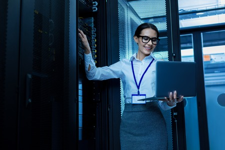 Happy beautiful woman working in a server cabinet and holding her laptop