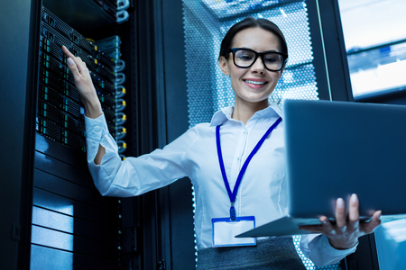 Content attractive woman working in a server cabinet and holding her laptop Banco de Imagens