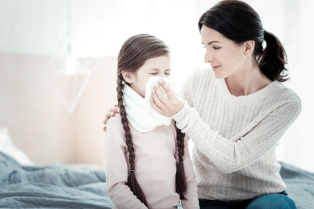 Im with you. Caring attentive pleasant mother sitting on the bed near her ill daughter hugging her and holding a napkin.