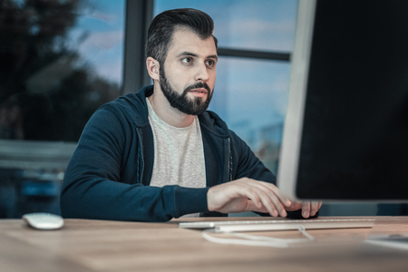 Computer command. Attentive pensive IT guy typing while posing in front of window and looking at screen