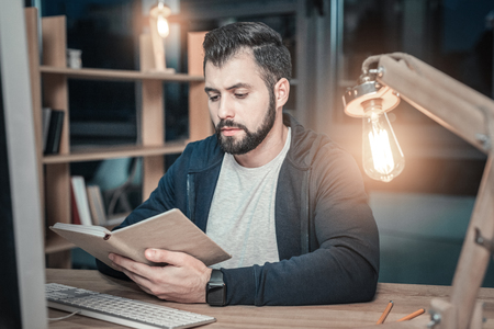 More theoretical information. Skillful attractive IT guy holding book while examining it and looking down Stock Photo