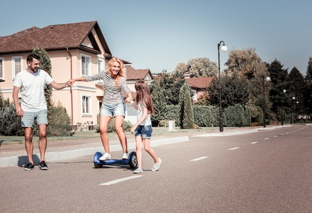 Hold my hand. Satisfied pretty unconfident woman riding on the self-balancing scooter having fun. Stock Photo