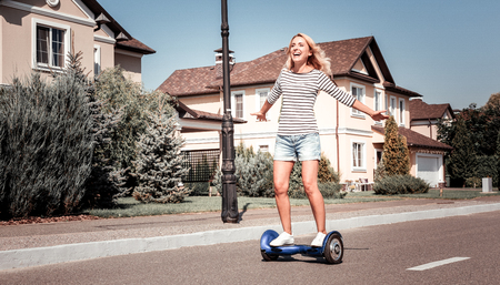 I am free. Joyful pleasant amazed woman riding on the self-balancing scooter shaking hands and rejoicing. Stock Photo