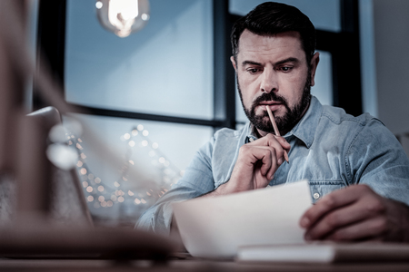 Pay attention. Occupied thoughtful beardful man working by the table holding panicle near mouth reading the letter. Stock Photo