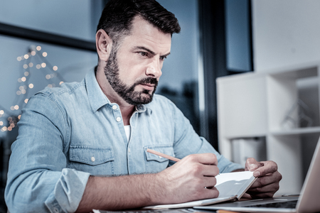 Full concentration. Serious occupied unshaken employee sitting in his cabinet by the table looking at the screen of his laptop and making notes.