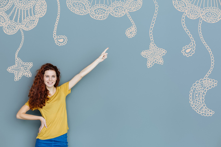 Showing stars. Cheerful creative designer pointing her finger up while showing beautiful stars on the wall