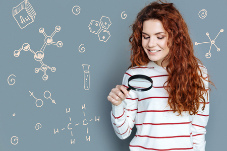 Interesting chemistry. Cheerful diligent student holding a magnifying glass and enjoying the lesson of chemistry Stock Photo