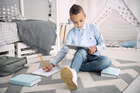Online learning. Focused afro american boy performing task while using tablet