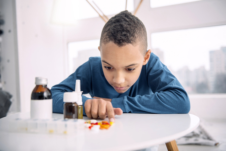 Serious afro american boy looking at pills while pointing with finger